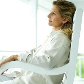 Woman sitting in rocking chair on porch, side view